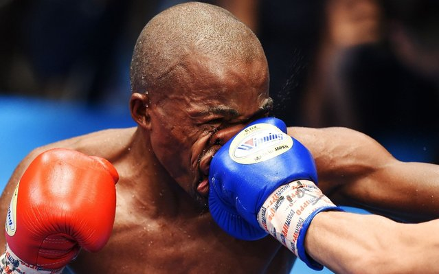 Moruti Mthalane of South Africa is punched by Masayuki Kuroda of Japan during their IBF flyweight title boxing bout in Tokyo on May 13, 2019. (Photo by Charly Triballeau/AFP Photo)