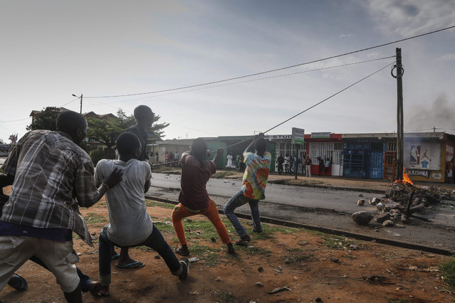 Burundian protesters pull electrical cable to topple the power pole, during an anti-government demonstration in the capital Bujumbura, Burundi, 21 May 2015. The Red Cross said two protesters had been killed during protests against Nkurunziza's bid for a third term on 21 May. (Photo by Dai Kurokawa/EPA)