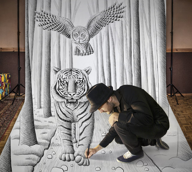 "Visual artist Ben Heine at work in his studio while he creates one of his ""anamorphic illusions"" in Rochefort, Belgium"