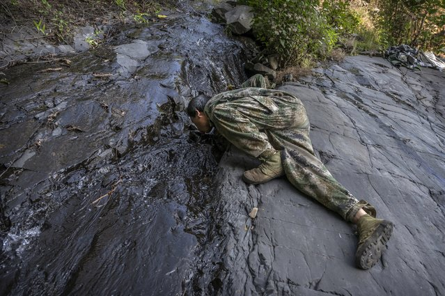 Chinese ethnic Lisu honey hunters Ma Yongde takes a drink from a stream after gathering wild cliff honey from hives in a gorge on May 31, 2019 near Mangshi, in Dehong prefecture, Yunnan province China. (Photo by Kevin Frayer/Getty Images)