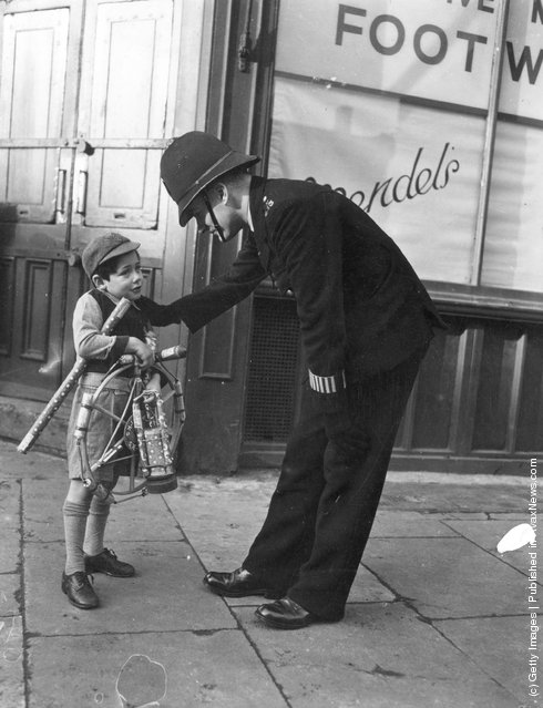 1951: A policeman offering a cautionary word of advice to a school child laden with fireworks before Guy Fawkes day, Britain's national firework festival