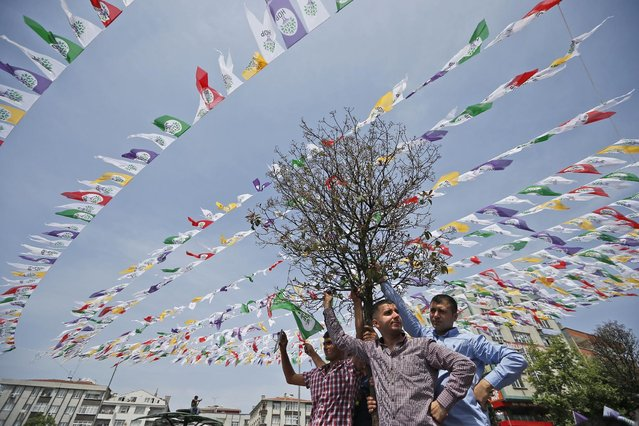 Supporters of Selahattin Demirtas, co-chair of the the pro-Kurdish People's Democratic Party (HDP) wait for him to arrive to deliver a speech during a rally in Istanbul, Turkey, Sunday, May 24, 2015. Turkey will hold general election on June 7, 2015. Although it is a relatively small party, all eyes will be on HDP. (Photo by Emrah Gurel/AP Photo)
