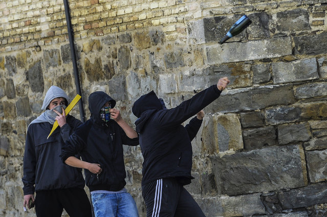 A masked student, centre, throws a bottle towards riot police, during the second day of protests, in Pamplona northern Spain, Thursday, March 27, 2014. Hundreds of Spanish students took part in a general strike to protest government education reform and cutbacks plan. (Photo by Alvaro Barrientos/AP Photo)