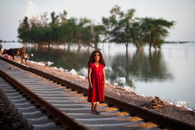 A girl stands near flood waters in a flood-hit village called Bamdezh in Khuzestan province, Iran, on April 10, 2019. Residents of Bamdezh village have been relocated to a freight train cabin by the authorities after their houses were surrounded by flood. (Photo by Ahmad Halabisaz/Xinhua News Agency/Barcroft Images)