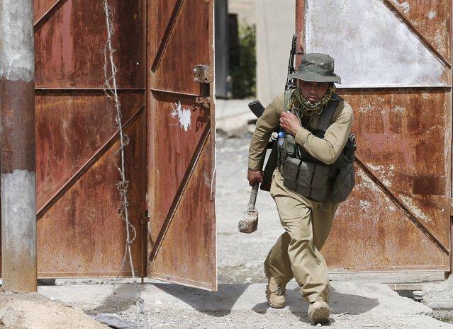 A Kurdish gunman runs for cover during clashes with Shi'ite militiamen in Tuz Khurmato, Iraq, April 24, 2016. (Photo by Goran Tomasevic/Reuters)