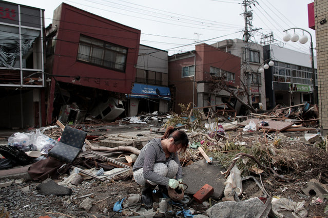 A woman sifts through the rubble of her home on March 17, 2011 in Kensennuma, Japan. Residents were allowed back to their homes today and began the massive cleanup operation caused by a 9.0 magnitude strong earthquake that struck on March 11 off the coast of north-eastern Japan. The quake triggered a tsunami wave of up to 10 metres which engulfed large parts of north-eastern Japan. The death toll has risen past 5000 with at least 8600 people still missing. (Photo by Chris McGrath/Getty Images)