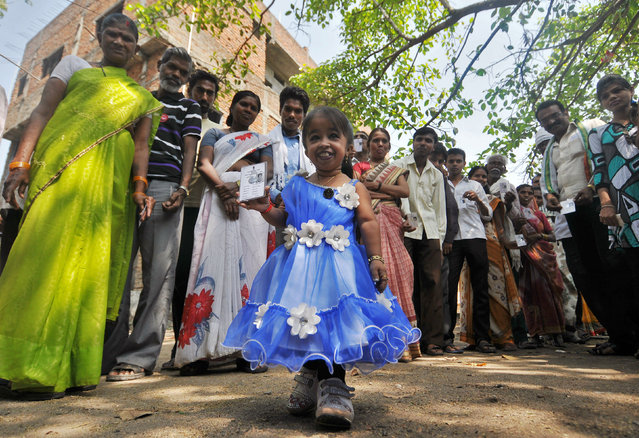 Jyoti Amge, 20, a first time voter, shows her voting card as she arrives to cast her vote in the central Indian city of Nagpur April 10, 2014. Amge has been certified by the Guinness World Records as the shortest woman in the world. Around 815 million people have registered to vote in the world's biggest election – a number exceeding the population of Europe and a world record - and results of the mammoth exercise, which concludes on May 12, are due on May 16. (Photo by Reuters)