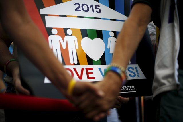 A couple hold hands at a celebration rally in West Hollywood, California, United States, June 26, 2015. (Photo by Lucy Nicholson/Reuters)
