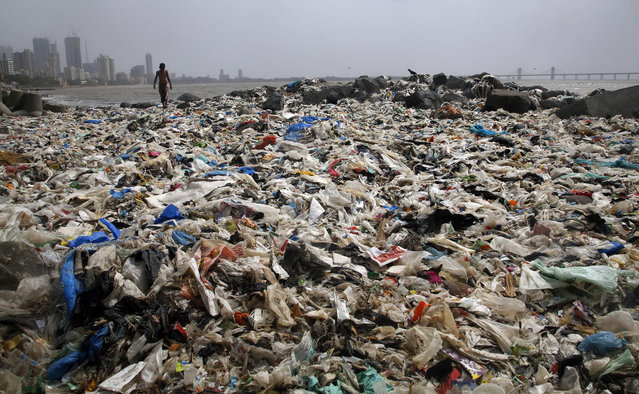 An Indian boy walks by the Arabian Sea coast piled with garbage, mostly plastic waste, in Mumbai, India, Friday, June 26, 2015. Several recent reports have highlighted India's worsening air quality and termed its capital New Delhi the worst polluted city in the country. In the last decade, along with India's economic boom and increasing prosperity, the output of garbage has also increased manifold. (Photo by Rajanish Kakade/AP Photo)