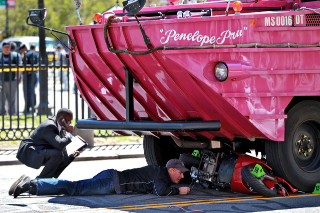 Investigators work the scene of an accident involving a Duck Boat on Saturday, April 30, 2016 in Boston. A  woman has died after the scooter she was driving was struck by an amphibious sightseeing vehicle in downtown Boston. A city police department spokeswoman said the woman and her male passenger were taken to Massachusetts General Hospital, where the woman died from her injuries. The passenger suffered non-life threatening injuries. (Photo by Jonathan Wiggs/The Boston Globe via AP Photo)