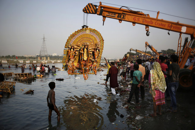 In this Tuesday, October 11, 2016 file photo, a giant Idol of Hindu goddess Durga suspends from a crane before it is immersed in the River Yamuna during Durga Puja festival in New Delhi, India. A court in northern India has granted the same legal rights as a human to the Ganges and Yamuna rivers, considered sacred by nearly a billion Indians. The Uttaranchal High Court in Uttarakhand state ruled Monday, March 20, 2017,  that the two rivers be accorded the status of living human entities, meaning that if anyone harms or pollutes the rivers, the law would view it as no different from harming a person. (Photo by Altaf Qadri/AP Photo)