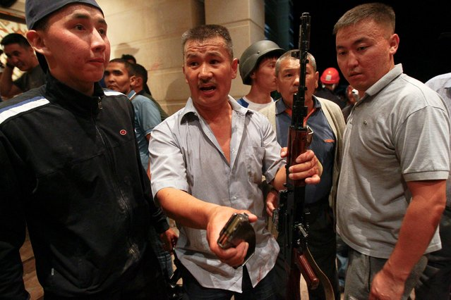 Armed supporters of Almazbek Atambayev guard his house in the village of Koi Tash near Bishkek, Kyrgyzstan August 7, 2019. The Kyrgyz State Committee on National Security confirmed its special forces unit was seeking to detain Atambayev at the village outside the capital Bishkek and had used rubber bullets. An Atambayev-controlled television station, April, broadcast footage in which gunshots could be heard and armed men seen around the building wearing camouflage and bulletproof vests. (Photo by Vladimir Pirogov/Reuters)