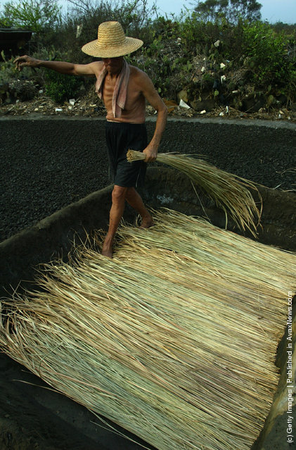 A villager prepares straw at ancient salt fields in Yantian Village on Hainan Island, China