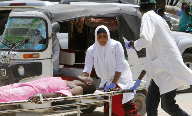Medical workers help a man who was wounded in a car bomb attack, at Medina hospital, in Mogadishu, Somalia, Monday, July 22, 2019. A Somali police officer says a car bomb in the Somali capital has killed at least 10 people. Capt. Mohamed Hussein said at least 15 others were injured when the car bomb parked near a busy security checkpoint on the city's airport was detonated by remote control. (Photo by Farah Abdi Warsameh/AP Photo)