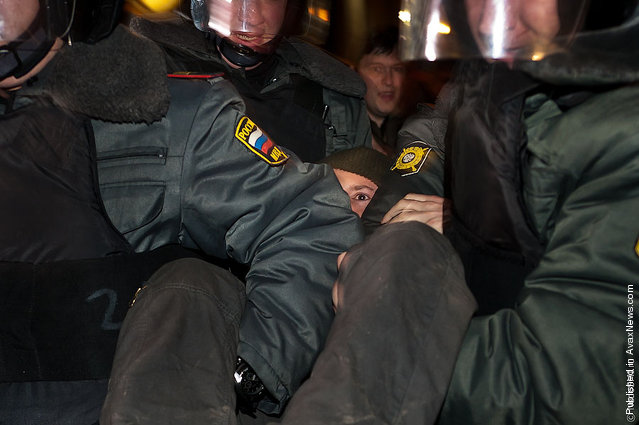 Police officers carry an opposition activist, who was detained while taking part in an unauthorized rally, at the Triumfalnaya Square in central Moscow