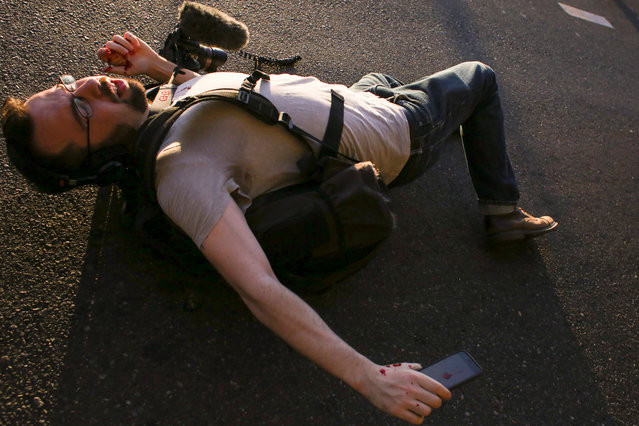 A man lies in the street after being struck in the face by an object during anti-capitalist protests following May Day marches in Seattle, Washington, U.S. May 1, 2016. (Photo by David Ryder/Reuters)