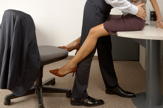 Low section view of a businessman and a businesswoman flirting in an office. (Photo by Getty Images)