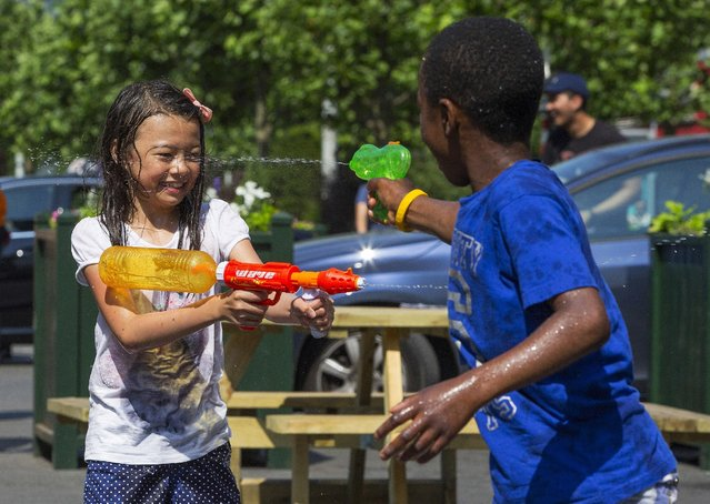 Children take part in a giant water fight on a hot summer day  in central Brussels, Belgium, July 3, 2015. (Photo by Yves Herman/Reuters)