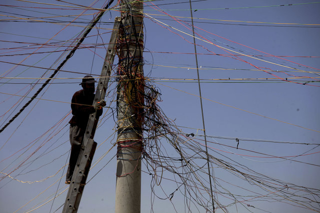 A man tries to connect his store with electricity from the main electricity pole at the Zaatari Refugee Camp, in Mafraq, Jordan, Tuesday April 22, 2014. An estimated 104,494 refugees reside in the sprawling Zaatari refugee camp, according to the United Nations High Commissioner for Refugees (UNHCR), with the majority of the population coming from the Daara Governorate in southwest Syria. (Photo by Mohammad Hannon/AP Photo)