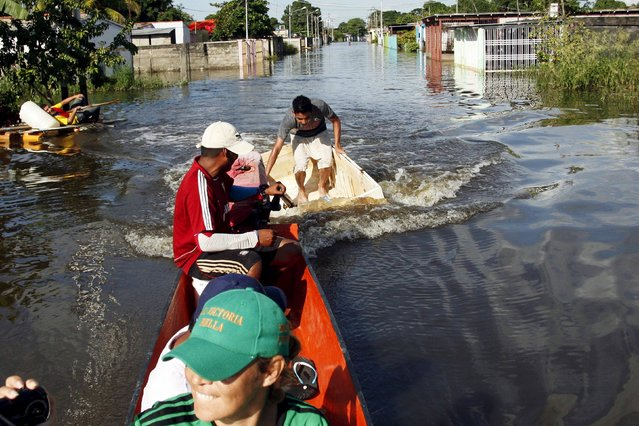 A man in a styrofoam box (C) is towed by a raft in a flooded street in Guasdualito, in the state of Apure, Venezuela, July 4, 2015. A total of 9,000 families have been affected by the overflowing of rivers Arauca and Sarare in Guasdualito, Apure state, because of the heavy rains in recent days in this area of the country, local media reported. (Photo by Carlos Eduardo Ramirez/Reuters)