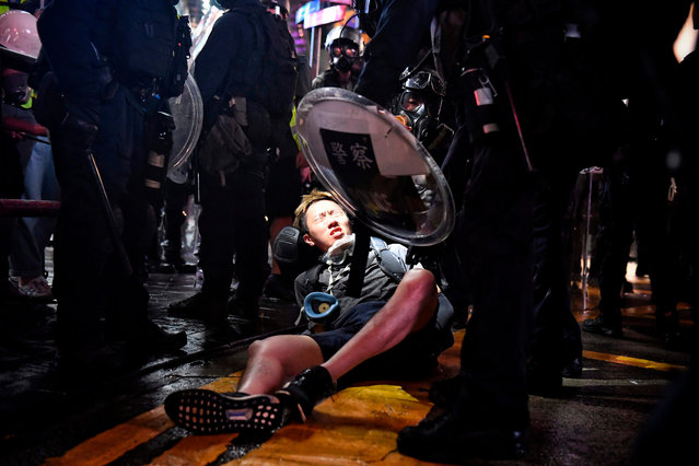 A protester is detained at Causeway Bay in Hong Kong on August 31, 2019, in the latest opposition to a planned extradition law that has since morphed into a wider call for democratic rights in the semi-autonomous city. Chaos engulfed Hong Kong's financial heart on August 31 as police fired tear gas and water cannon at petrol bomb-throwing protesters, who defied a ban on rallying – and mounting threats from China – to take to the streets for a 13th straight weekend. (Photo by Lillian Suwanrumpha/AFP Photo)