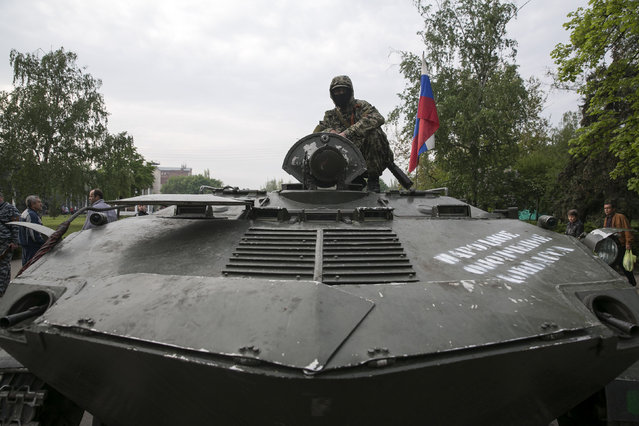A pro-Russian separatist stands guard on top of an armoured personnel carrier in the town of Slaviansk in eastern Ukraine May 2, 2014. (Photo by Baz Ratner/Reuters)