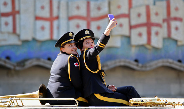 Two female members of a military band take a selfie picture at the Unknown Soldier Tomb memorial in Tbilisi on May 9, 2016, during Victory Day celebrations. Georgia and and ex-Soviet republics mark the 71st anniversary of the Soviet Union's victory over Nazi Germany in World War II. (Photo by Vano Shlamov/AFP Photo)
