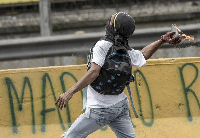 A demonstrator throws a Molotov cocktail in clashes with riot police during a protest against Venezuelan President Nicolas Maduro, in Caracas on April 20, 2017. (Photo by Carlos Becerra/AFP Photo)