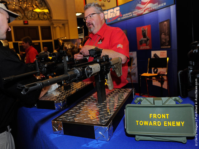 Brant Sabau with GG&G Inc. talks to attendees about the company's tactical rifle accessories behind an Airsoft AR-15 rifle and a replica claymore anti-personnel mine