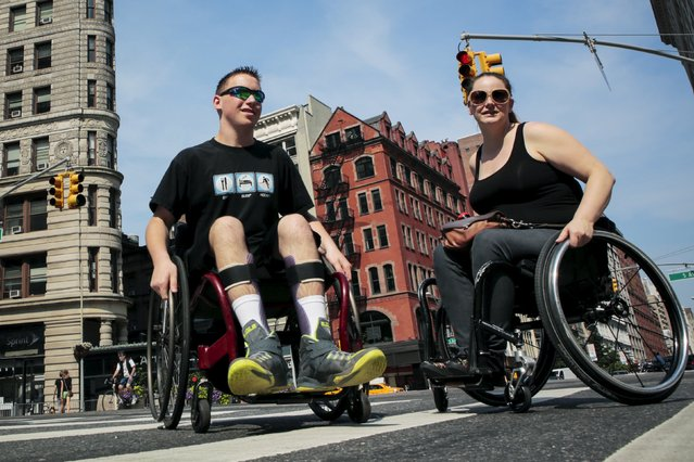 Sara Tabor (R), 33, suffering from paraplegia, and Matt Castagna, 15, suffering from cerebral palsy arrive to take part in the disability pride parade in New York, July 12, 2015. (Photo by Eduardo Munoz/Reuters)