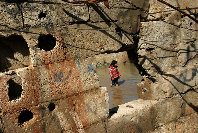 A Palestinian girl is seen through a hole in a wall as she wades through floodwaters following a rainstorm, in the northern Gaza Strip February 17, 2017. (Photo by Mohammed Salem/Reuters)