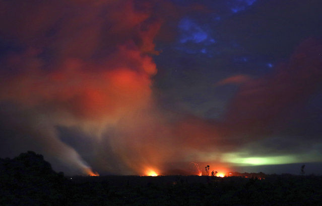 In this May 15, 2018 file photo, lava shoots into the night sky from active fissures on the lower east rift of the Kilauea volcano near Pahoa, Hawaii. A year after a Hawaii volcano rained lava and gases on a rural swath of the Big Island in one of its largest eruptions in recorded history, people who lost their homes and farms in the disaster are still struggling to return to their island lifestyle. More than 700 homes were destroyed in the historic eruption, and most people will never move back to their land. (Photo by Caleb Jones/AP Photo/File)