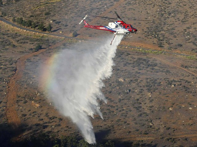 A helicopter drops water on a burning canyon next to homes as firefighters battle the Bernardo Fire, north of San Diego, California. (Photo by Mike Blake/Reuters)