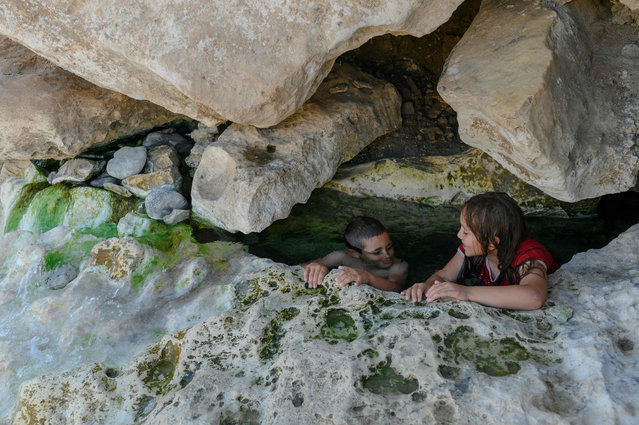 Muhammed (L) and Hasret (R) enjoy a hot spring water in the Botan valley a few kilometers from the Ilisu dam, next to the city of Siirt on August 18, 2019. (Photo by Bülent Kılıç/AFP Photo)