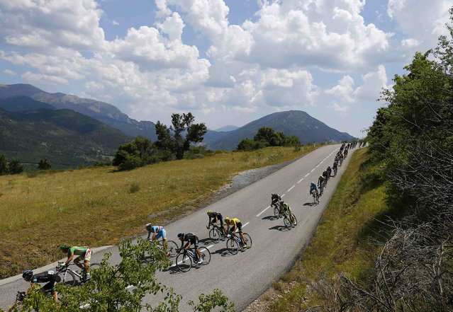 Team Sky rider Chris Froome of Britain (C), the race leader's yellow jersey, cycles with the pack of riders during the 161-km (100 miles) 17th stage of the 102nd Tour de France cycling race from Digne-les-Bains to Pra Loup in the French Alps mountains, France, July 22, 2015. (Photo by Stefano Rellandini/Reuters)