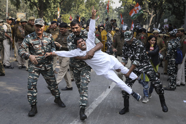 Indian paramilitary soldiers detain a Congress party supporter during a protest against the withdrawal of Special Protection Group (SPG) cover to party president Sonia Gandhi, her children Rahul Gandhi and Priyanka Vadra and former prime minister Manmohan Singh, in New Delhi, India, Wednesday, November 20, 2019. The move to lift off the SPG security, an elite force that protects prime ministers and their immediate families, led to sharp reactions from the Congress, which accused the government of personal vendetta. (Photo by Altaf Qadri/AP Photo)