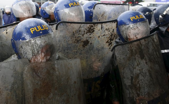 Policemen seek cover with their helmets and shields as they block protesters trying to march towards Batasang Pambansa, where Philippines President Benigno Aquino will address the joint session of Congress and deliver his last State of the Nation address in Quezon city, Metro Manila, Philippines July 27, 2015. (Photo by Erik De Castro/Reuters)