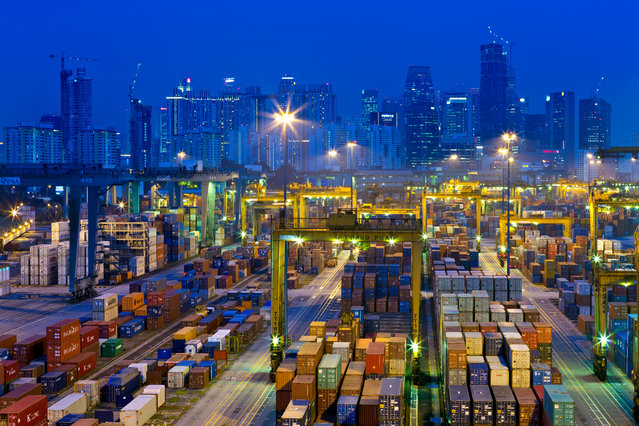 """""""Container City"""". Singapore, evening at Keppel Harbour container handling facility. Singapore is one of the world's busiest container ports and the leading transshipment port, in which containers are shuffled from one ship to another within the port. Photo location:  Singapore. (Photo and caption by John Seaton Callahan/National Geographic Photo Contest)"""