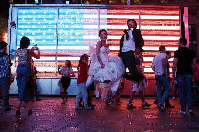 A newly married couple from Japan jump in the air as they pose for photos for their wedding photographer in Times Square in the Manhattan borough of New York, U.S., May 25, 2016. (Photo by Carlo Allegri/Reuters)