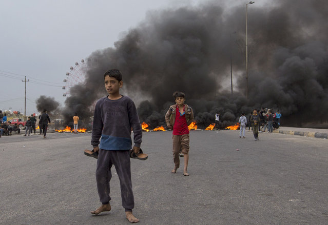 Iraqi children play on a street blocked with burning tyres, amid a general strike in the southern city of Basra, on November 25, 2019. The demonstrations rocking the capital and Shiite-majority south since October 1 are the biggest grassroots movement the country has seen in decades. Sparked by outrage over rampant government corruption, poor services and lack of jobs, they have since gone straight to the source: calling out the ruling system as inherently flawed and in need of a total overhaul. (Photo by Hussein Faleh/AFP Photo)