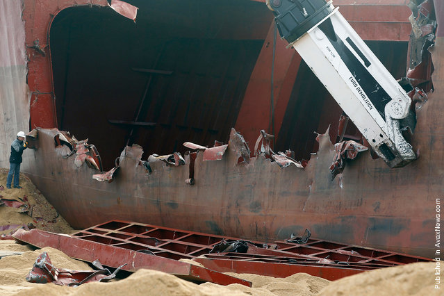 A closer view of the hydraulic shear cutting apart the hull and dismantling the TK Bremen on Kerminihy beach, on January 7, 2012