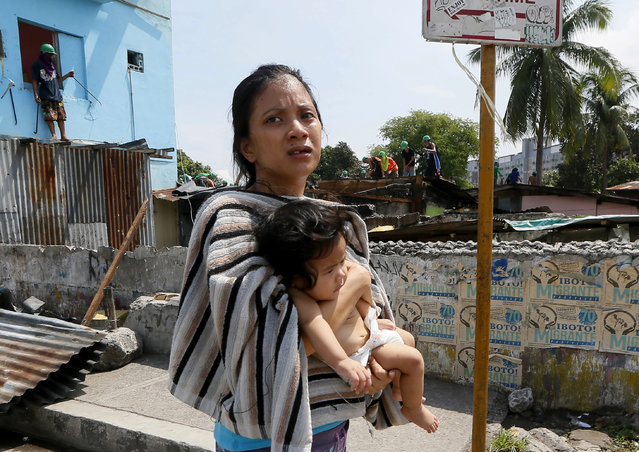 A mother carries her child as she walks away from her shanty home as demolition teams remove her makeshift community Monday, June 6, 2016 at suburban Quezon city northeast of Manila, Philippines. There was little resistance from the remaining 200 informal settlers as the city government implemented the demolition order to pave way for the development of the area. (Photo by Bullit Marquez/AP Photo)