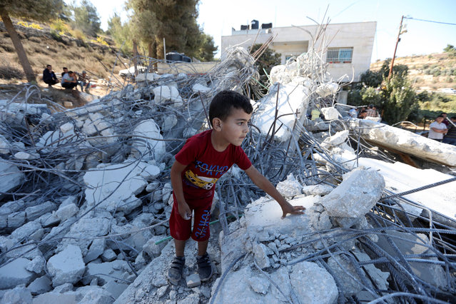 A Palestinian child stands on the rubble of a damaged under-construction building after Israeli bulldozers demolished in the West Bank village of Biet Ommar, north of Hebron, 03 October 2019. Israeli army regularly demolishes Palestinian buildings in area C of the West Bank because Palestinians do not have the Israeli needed permits to build. (Photo by Abed Al Hashlamoun/EPA/EFE)
