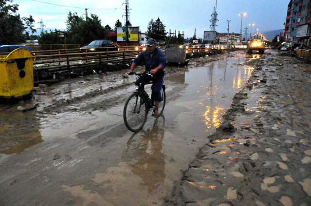 In this picture taken Monday evening, August 3, 2015, a man rides a bicycle along a muddy street after a flood in the town of Tetovo, northwestern Macedonia. At least four people, including three children, have died in floods that erupted after an hour of heavy torrential rains and strong winds that hit Tetovo and northwestern region of Macedonia late on Monday. (Photo by Zoran Andonov/AP Photo)