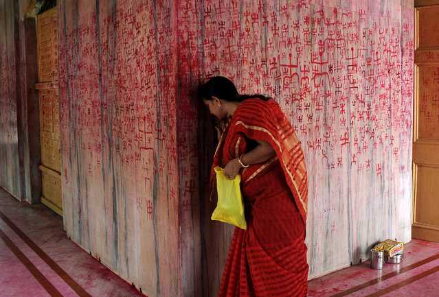 An Indian Hindu woman prays as she takes part in a ritual offering during the Ambubachi festival at a temple in Agartala, the capital of northeastern state of Tripura, on June 23, 2017. Hindu devotees celebrate the traditional Ambubachi festival to mark the menstruation period of the goddess Kamakhya. (Photo by Arindam Dey/AFP Photo)