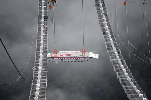 The installation of the first steel box girder onto a large-span suspension bridge over Longjiang River is seen in Baoshan, Yunnan province, July 30, 2015. (Photo by Reuters/Stringer)
