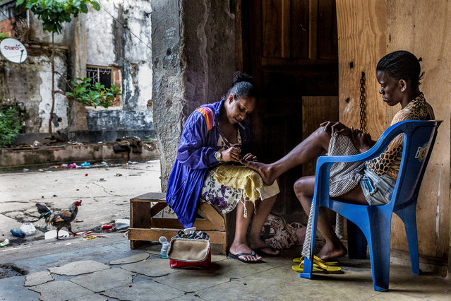 Ceia gives Alexandra a pedicure in the grounds of the building. (Photo by Tariq Zaidi/The Guardian)