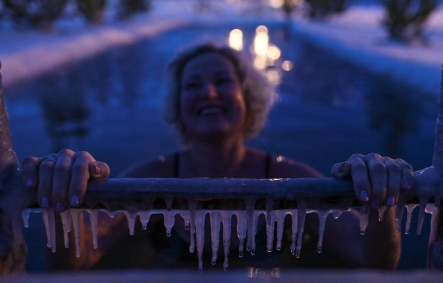A woman reacts while taking a dip in the freezing waters of the Irtysh River during celebrations of the Orthodox Christian feast of Epiphany in Omsk, Russia on January 18, 2020. (Photo by Alexey Malgavko/Reuters)