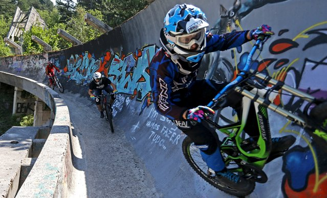 Downhill bikers Kemal Mulic (L-R), Tarik Hadzic and Kamer Kolar train on the disused bobsled track from the 1984 Sarajevo Winter Olympics on Trebevic mountain near Sarajevo, Bosnia and Herzegovina, August 8, 2015. (Photo by Dado Ruvic/Reuters)