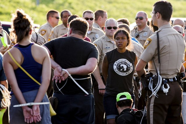 "Officers from the St Louis County Police Department and the Missouri Highway Patrol process demonstrators from the ""Black Lives Matter"" movement who had been arrested for protesting on Interstate 70 in Earth City, Missouri, August 10, 2015. (Photo by Lucas Jackson/Reuters)"